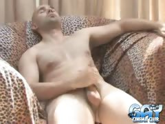 Hot bald gay Bucky wanking his enormous cock hard on the